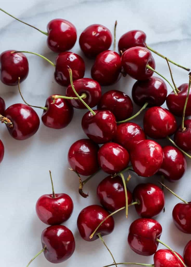 fresh cherries with stems on marble