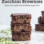 stack of three zucchini brownies with shredded zucchini and text overlay