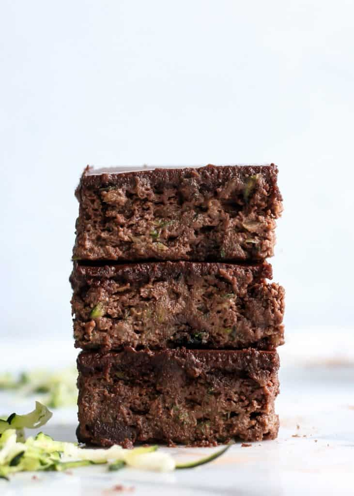 paleo vegan zucchini brownies in stack with spiralized zucchini