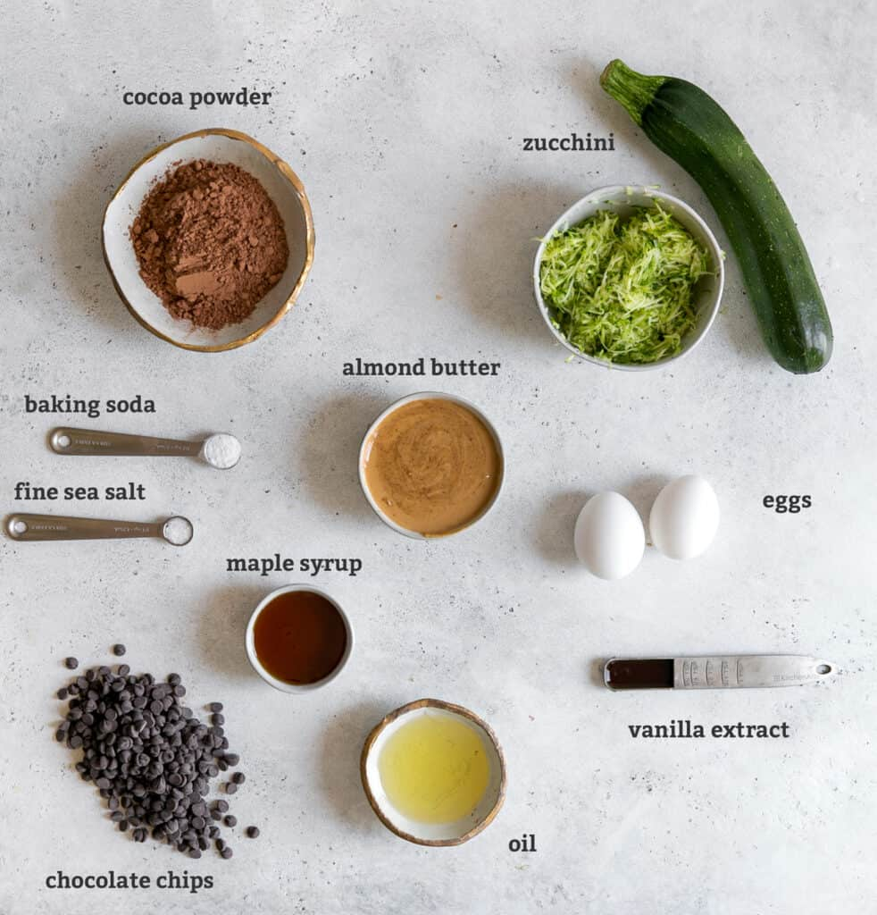 ingredients on board for zucchini brownies; cocoa powder, shredded zucchini, eggs, almond butter, vanilla, oil, maple syrup, chocolate chips, sea salt, baking powder