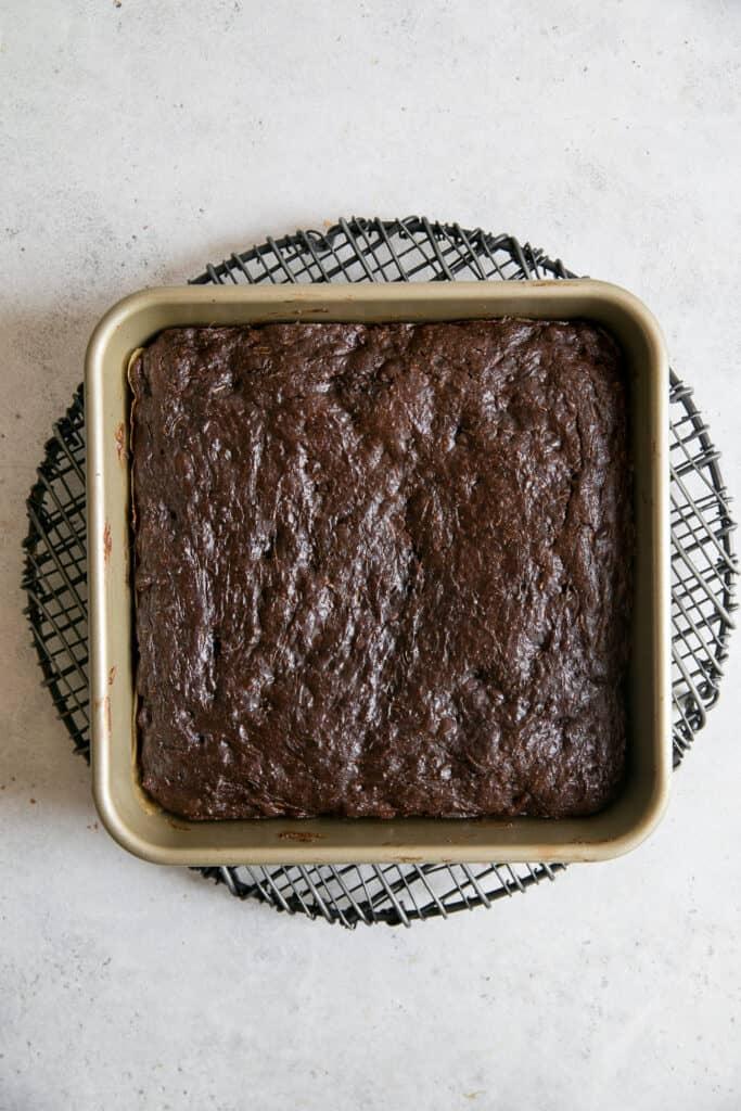 baked brownies in square pan on top of black cooling rack