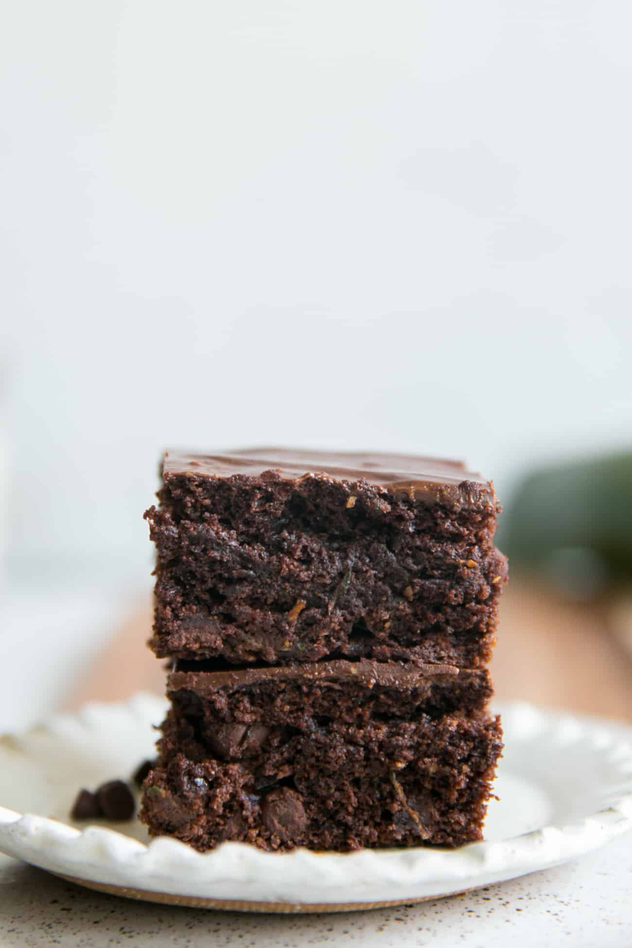 two stacked zucchini brownies on white plate