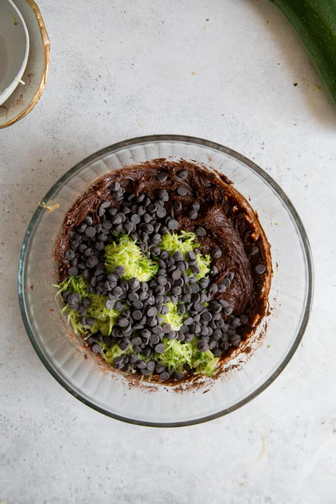 shredded zucchini and mini chocolate chips in brownie batter in glass bowl