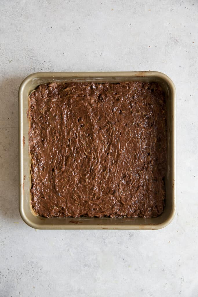 zucchini brownie batter in gold square pan