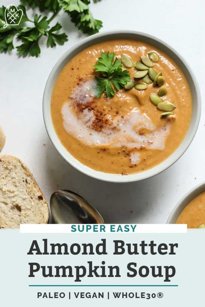 almond butter pumpkin soup in white bowl on countertop with slices of bread