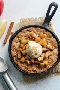 apple pie skillet cookie in cast iron skillet with ice cream
