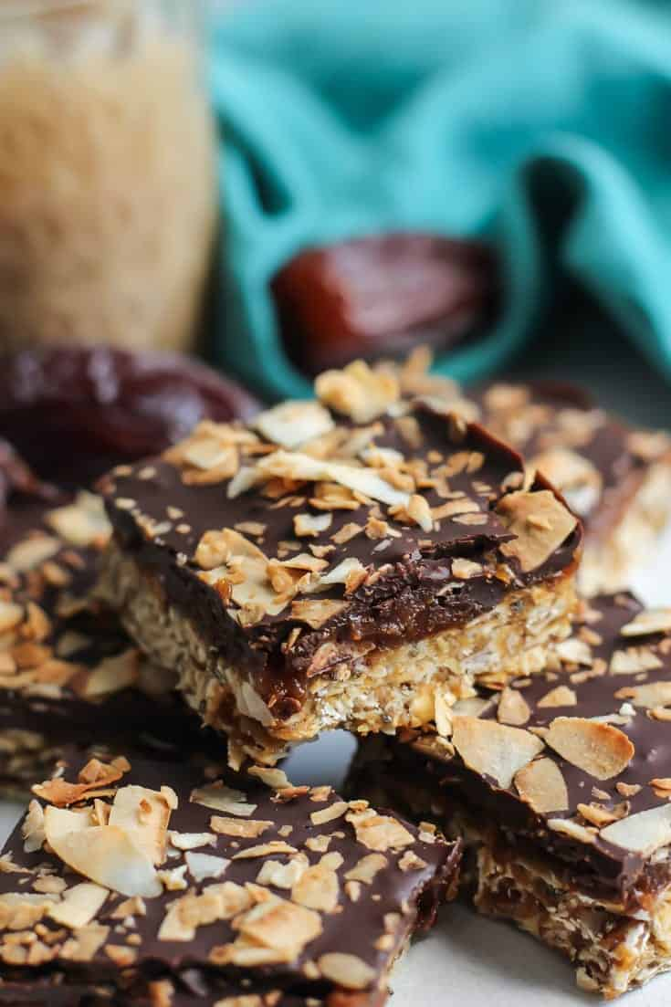 caramel filled coconut oat bars with chocolate topping.