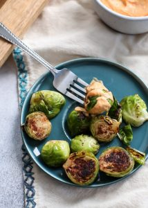 Stovetop Cinnamon Brussels Sprouts with Spicy Pumpkin Aioli on teal plate with fork
