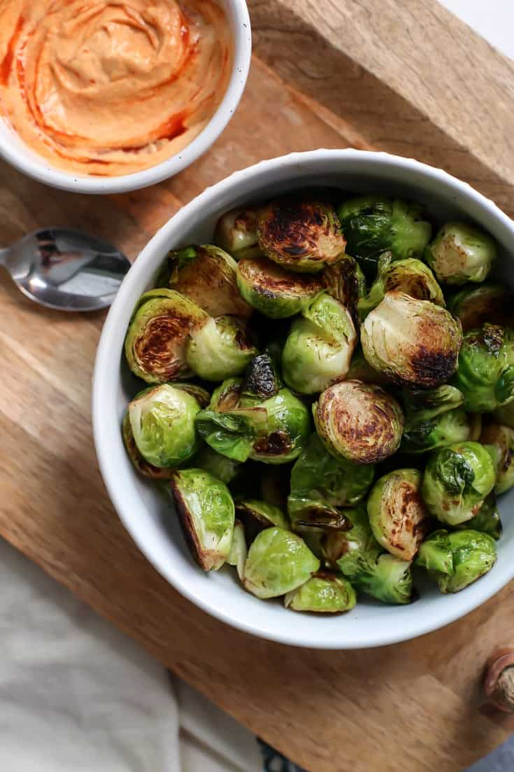 Cinnamon brussels sprouts and pumpkin aioli in white bowls on wooden tray
