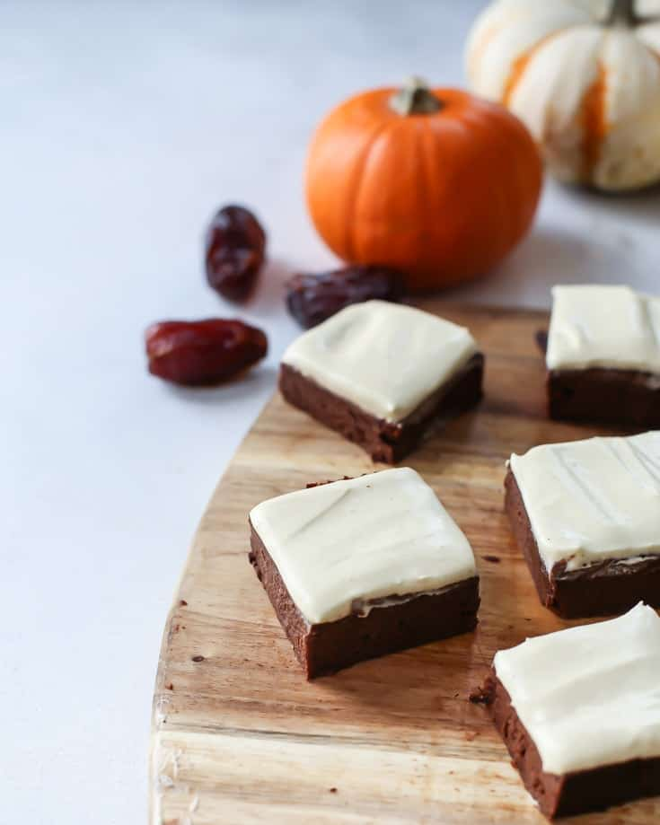 Paleo Fudgy Pumpkin Brownies with a pumpkin spice cream frosting on wooden platter