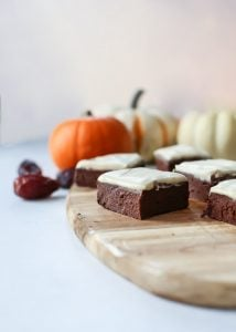 fudge pumpkin brownies with frosting on wooden tray with small pumpkinds