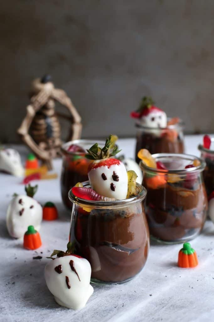 dirt pudding with white chocolate strawberry ghosts with gummy worms and pumpkin candy
