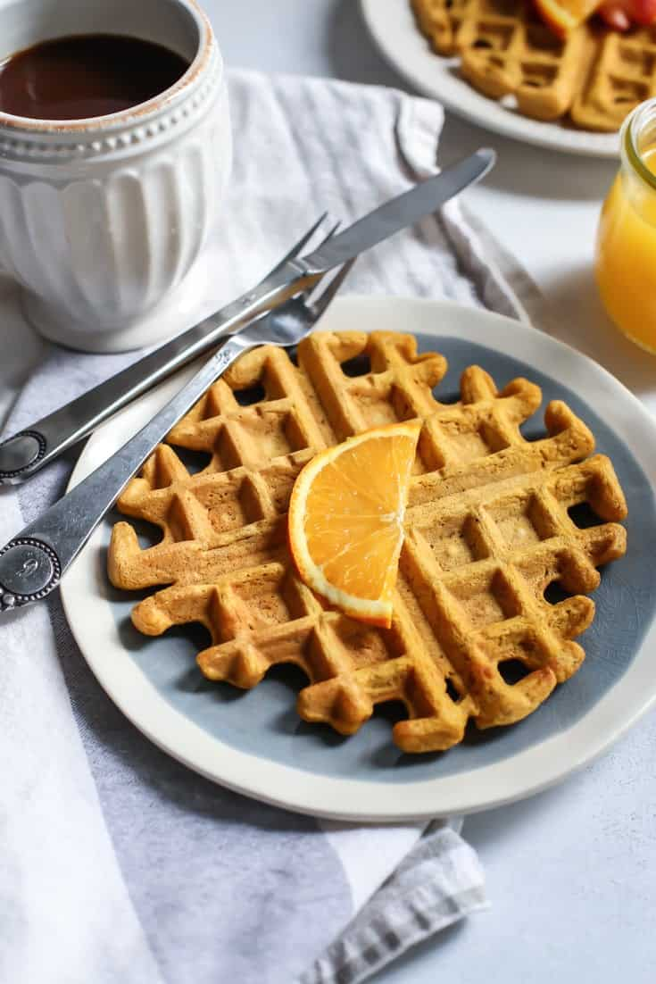 Healthy Pumpkin Spice Orange Waffles on plate with silverware on towel with coffee and orange juice