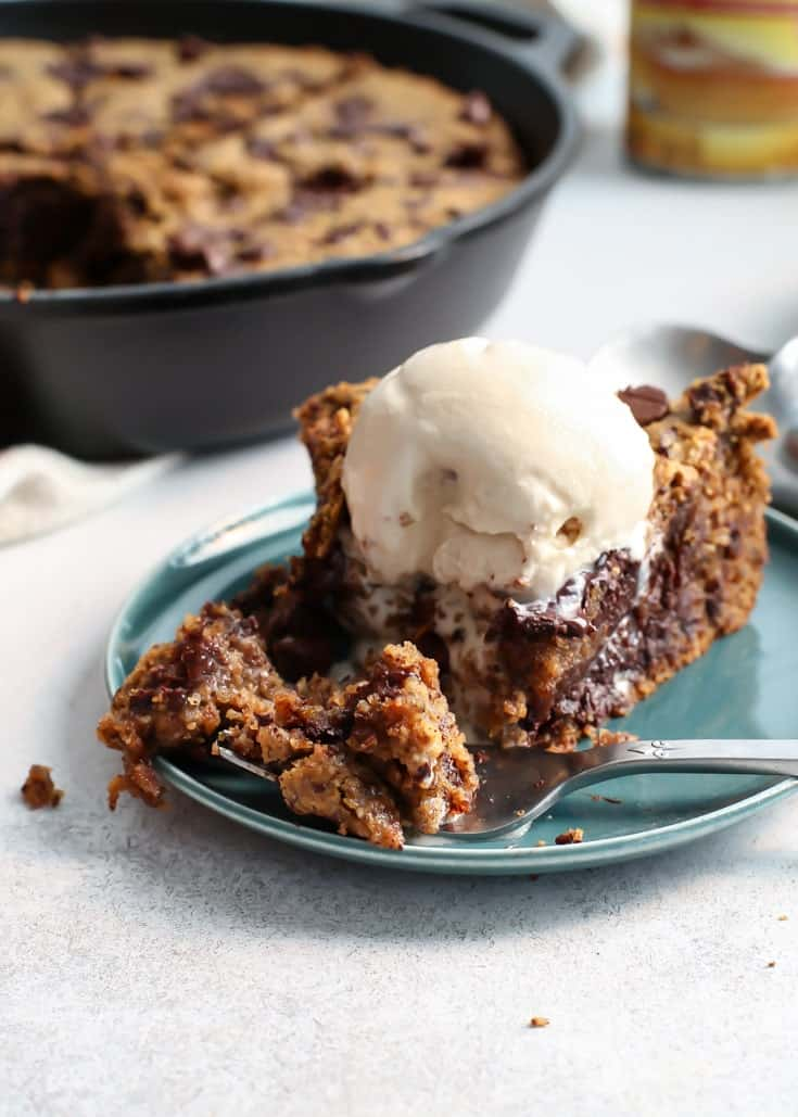 chocolate chip skillet cookie with ice cream on teal plate with fork and pumpkin puree