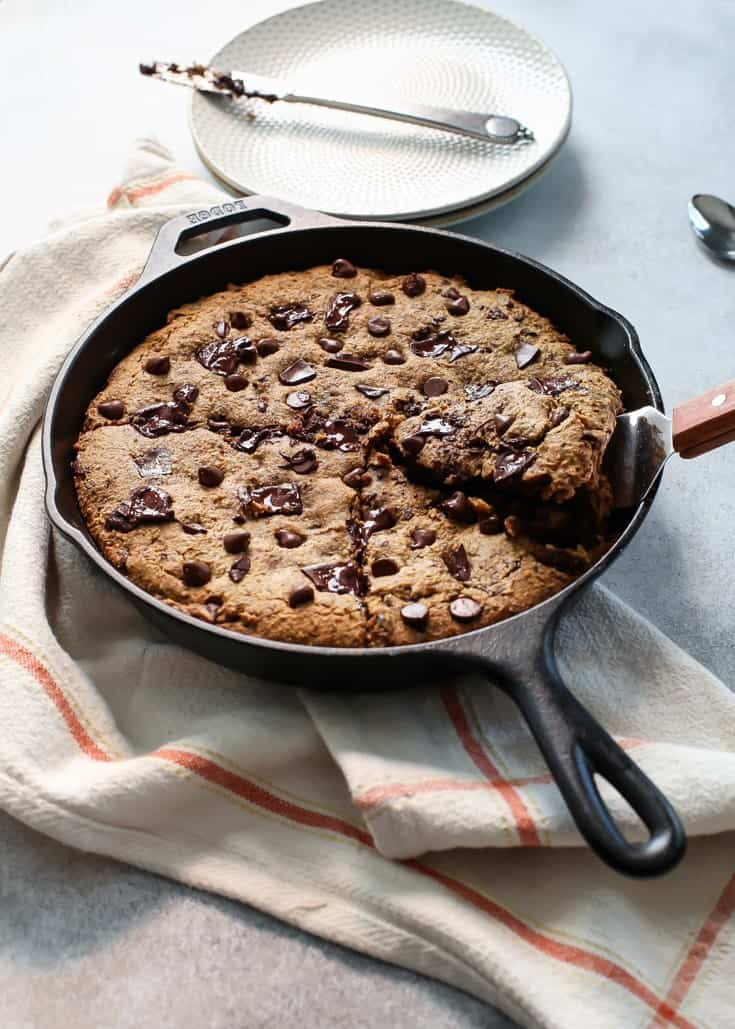 giant chocolate chip skillet cookie on orange and white towel with white plate and knife