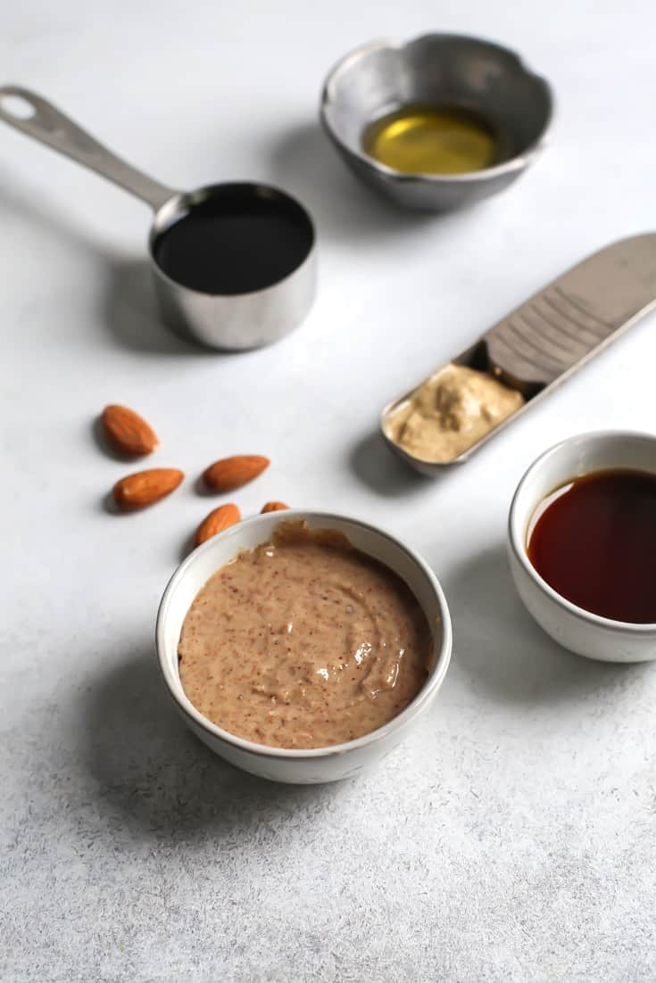 ingredients in measure cups and spoons - vinegar, almond butter, maple syrup, oil, and mustard