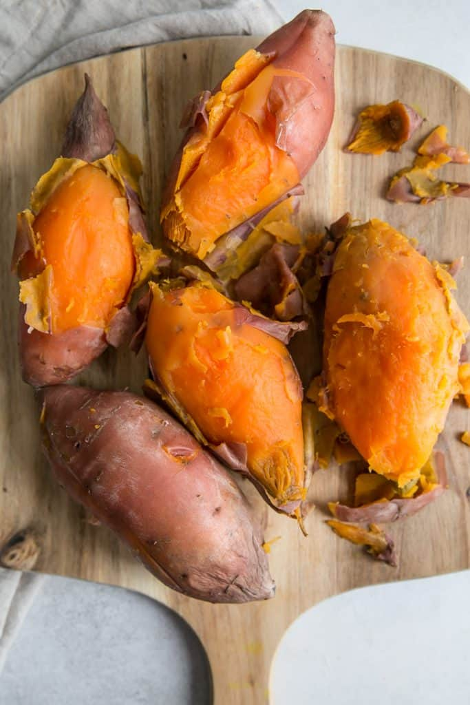 cooked sweet potatoes on board with skins