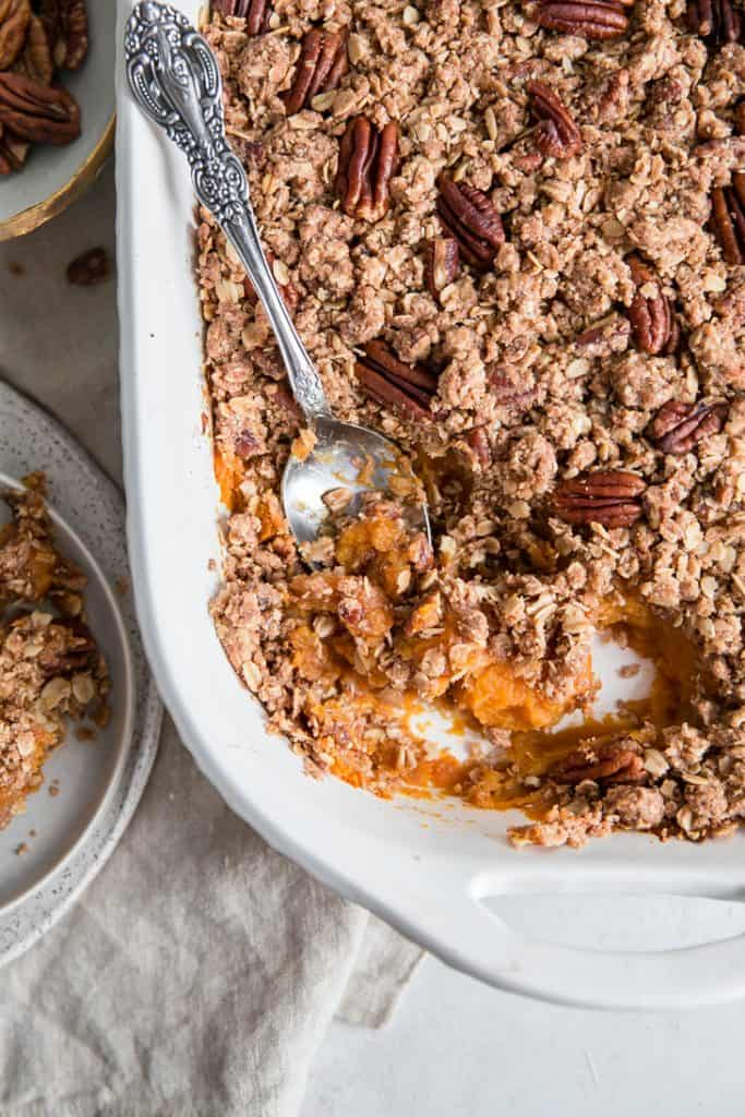 spoon digging into white casserole dish of sweet potatoes and pecans