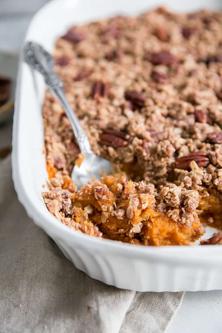 spoon digging into white casserole dish of sweet potatoes