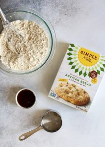 flour in glass bowl, Simple Mills bread mix box, maple syrup, measuring cup