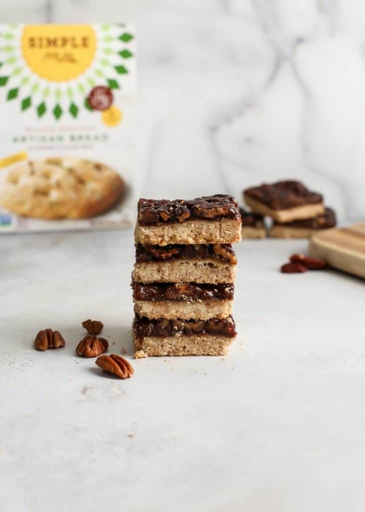 stack of four vegan pecan pie bars with gluten free Simple Mills box