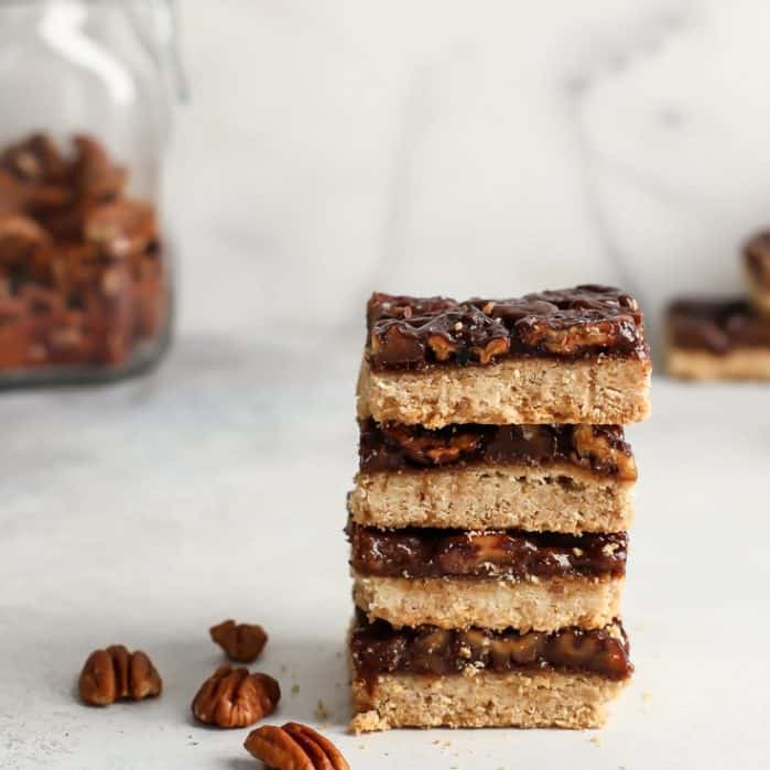 stack of four pecan pie bars with pecans in glass jar