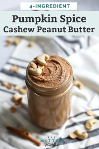 mason jar of pumpkin spice cashew peanut butter with cinnamon sticks and cashews