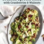 Serving dish of roasted brussels sprouts with apples, bacon and topped with pecans