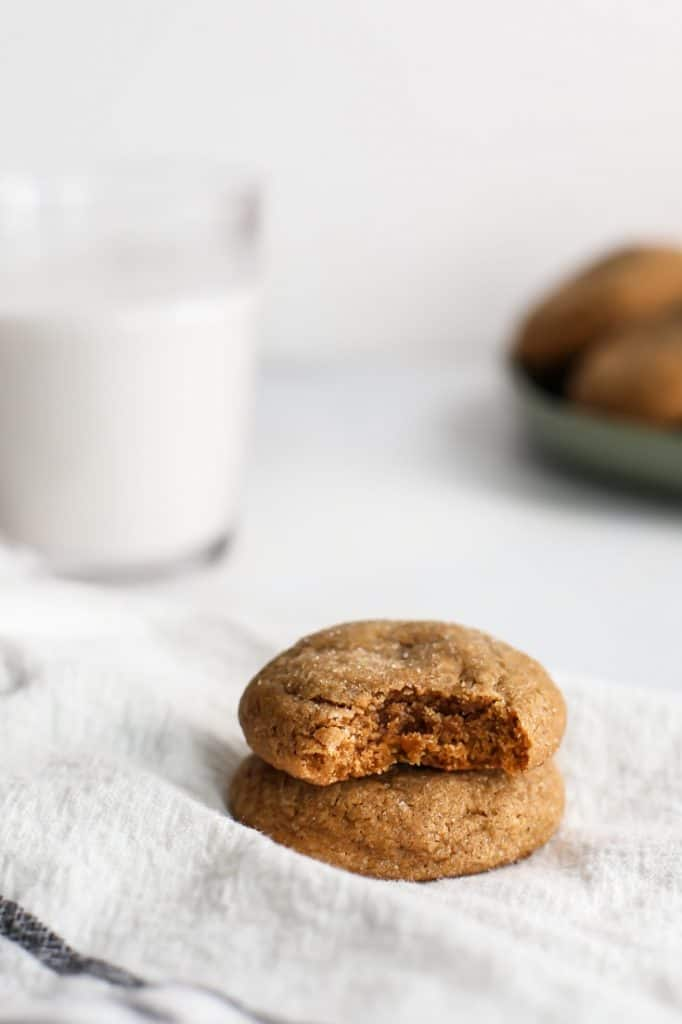soft and chewy gingerdoodle cookie with a bite and glass of milk