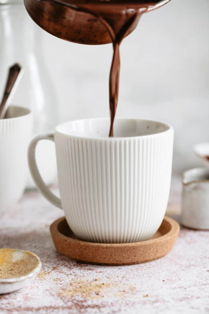 pouring hot chocolate into white mug