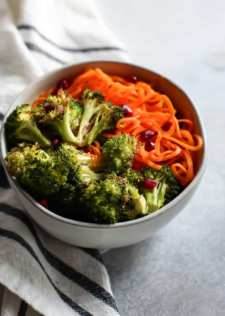 Vegan Buttery Garlic Roasted Broccoli with Sweet Potato Noodles (and pomegranate seeds!). Vegan and paleo friendly. The perfect side dish for healthy eating