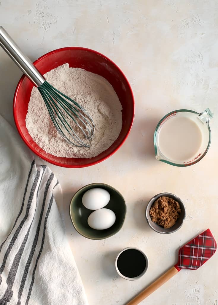Whole wheat pastry flour, baking powder, eggs, molasses, sugar and milk ingredients for waffles in red bowl