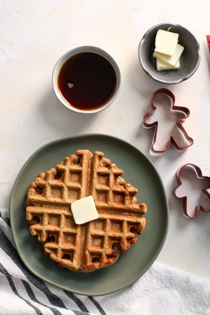 Whole Grain Gingerbread Waffles with maple syrup and butter on green plate with coffee and gingerbread cookie cutter