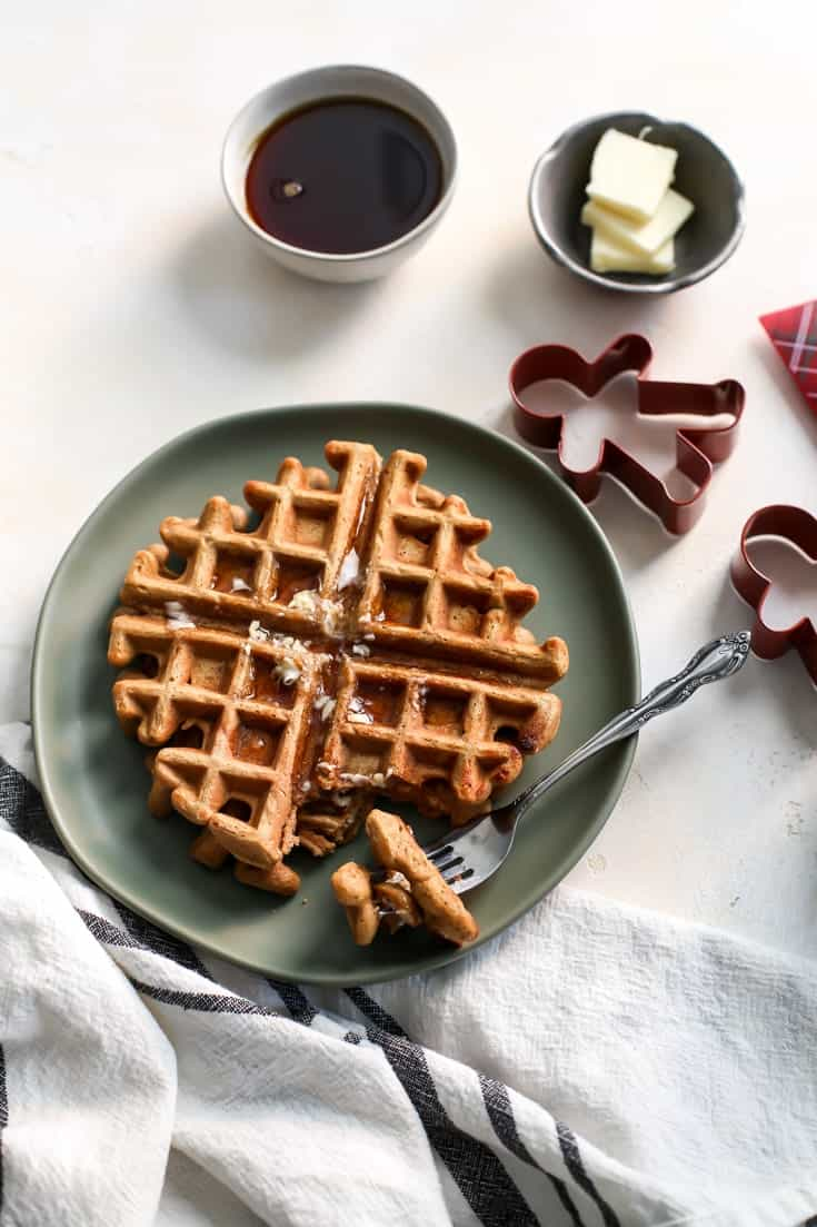 Whole Grain Gingerbread Waffles on green plate with maple syrup and gingerbread cookie cutters