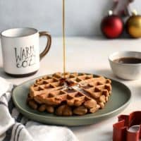 Whole Grain Gingerbread Waffles and maple syrup on green plate with coffee cup and Christmas cookie cutter decor