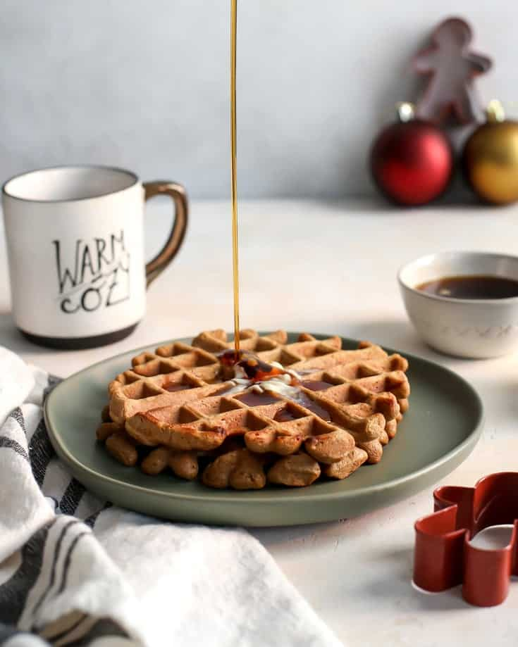 gingerbread waffles and maple syrup on green plate with coffee cup and Christmas cookie cutters