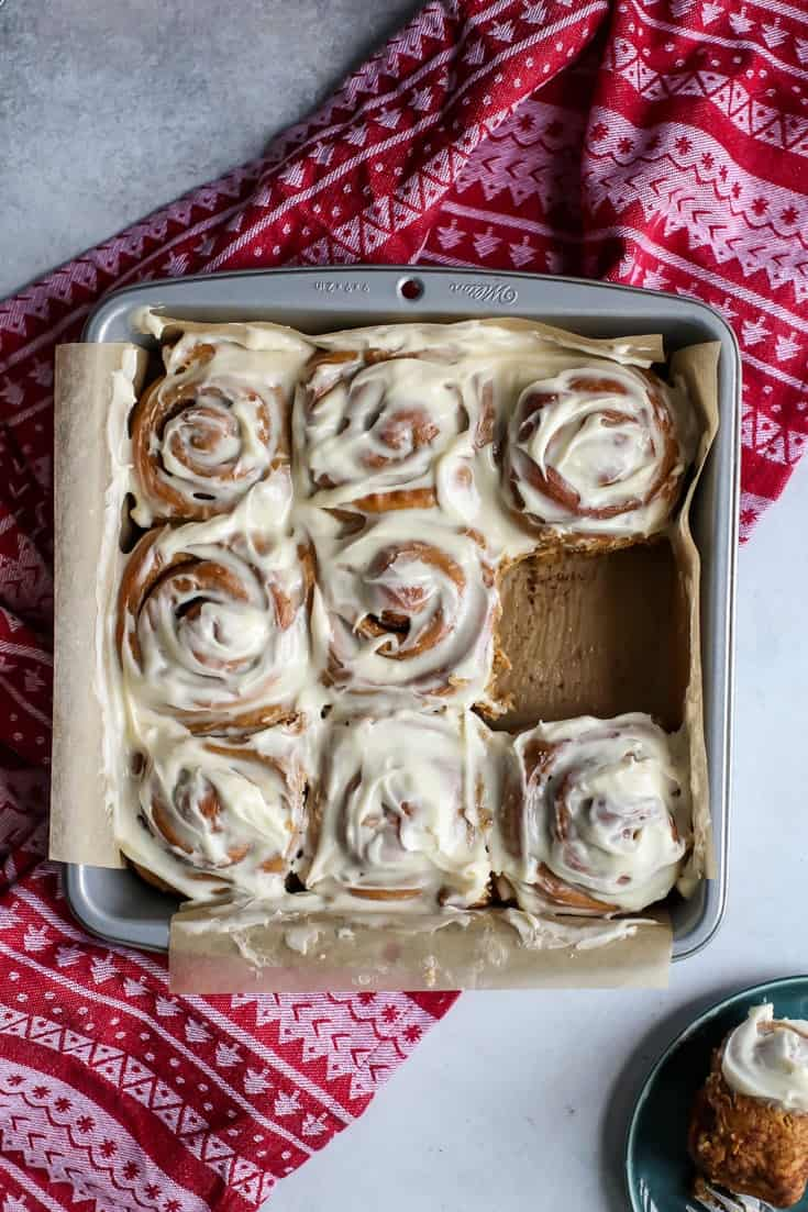 square pan of gingerbread cinnamon rolls on holiday towel