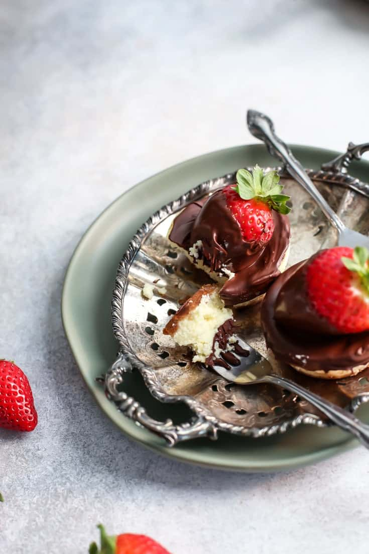 Chocolate Covered Strawberry Cheesecakes with fork on silver platter and green plate
