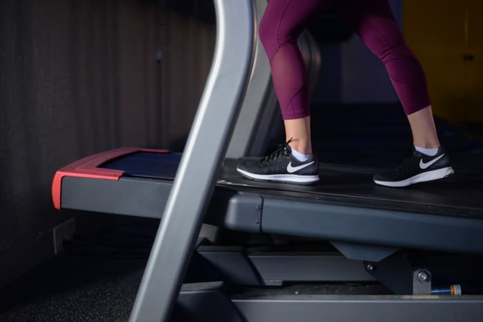 Nike Running Shoes with magenta crops on incline treadmill