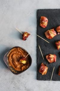 Bacon wrapped brussels sprouts on slate serving platter with almond butter dipping sauce in bowl