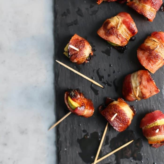 Bacon wrapped brussels sprouts on slate serving platter