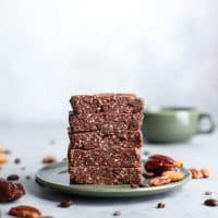 stack of cacao coffee protein bars on green saucer with green mug in background