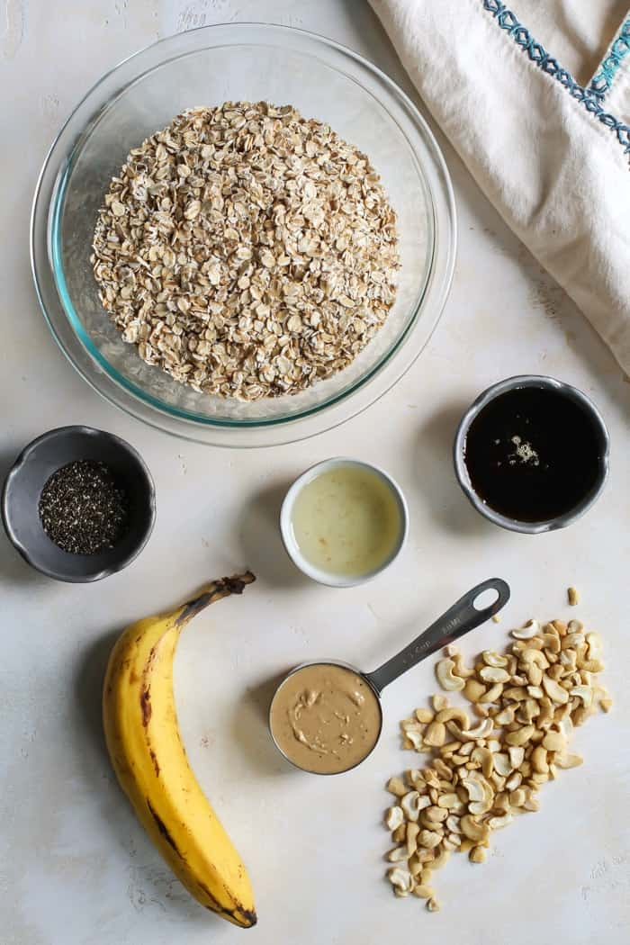 bowl of oats, chia seeds, coconut oil, maple syrup, cashew butter, banana and cashew pieces