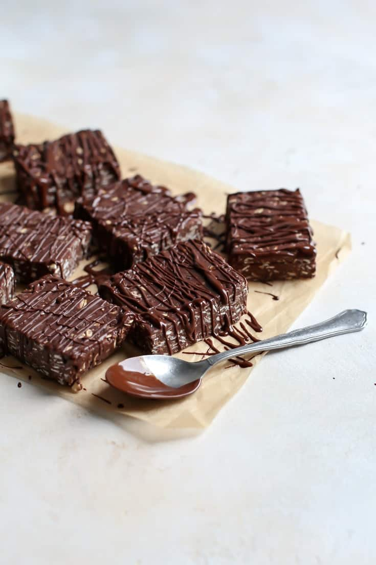 chocolate oat protein bars on parchment paper with chocolate and spoon