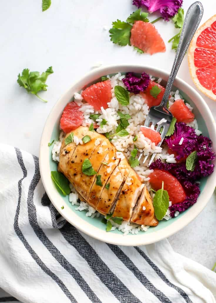 Glazed chicken with grapefruit, purple kale, coconut rice and mint in a bowl.