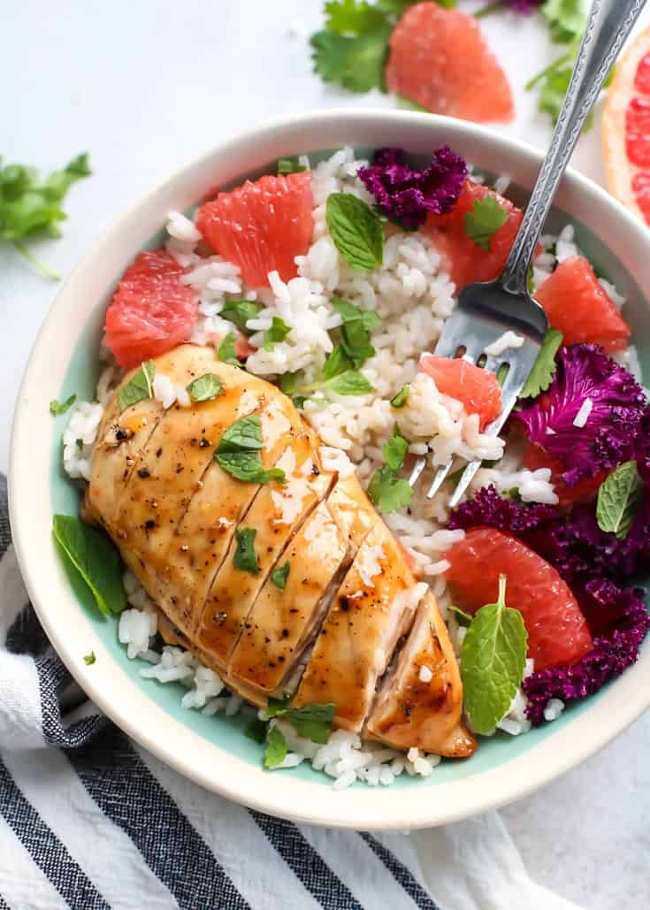 glazed chicken breast with grapefruit, rice, kale and mint in a bowl with a fork