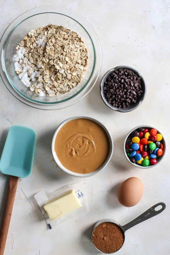 peanut butter, oats, chocolate chips, m&ms, egg and butter, measuring spoon and spatula for m&m cookies
