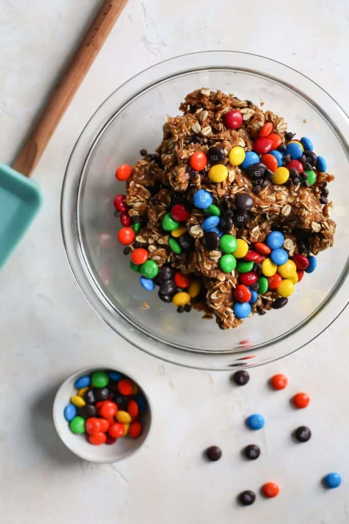 bowl of flourless monster cookie dough with m&ms and teal spatula