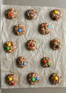 peanut butter m&m monster cookies on parchment paper cookie sheet