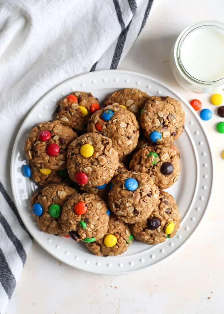 gluten free monster cookies on white plate with glass of milk and m&ms